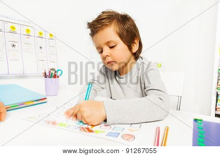Small boy draws with pencil on the paper sitting