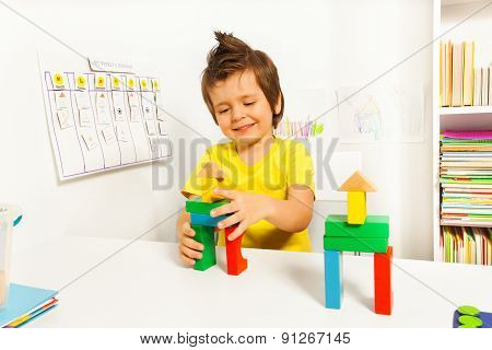 Cute boy putting blocks replicating example