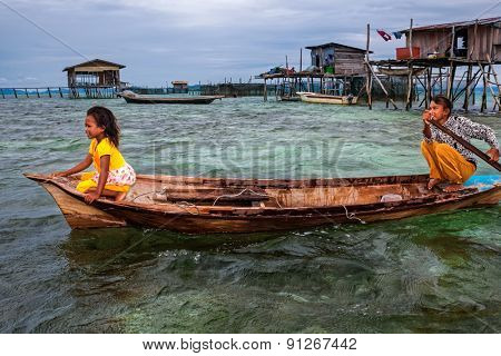 Sabah, Malaysia - September 10, 2011: Sea gypsies on the Borneo Island travel in the shallow seas using wooden paddle boats. They live in wooden houses built on stilts out in the sea.