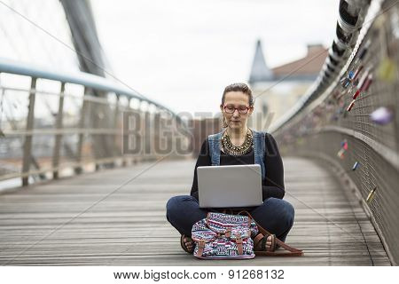 Young woman with laptop sitting on a pedestrian bridge. Freelancer.