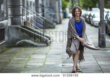 Young woman in a poncho walking down the street.