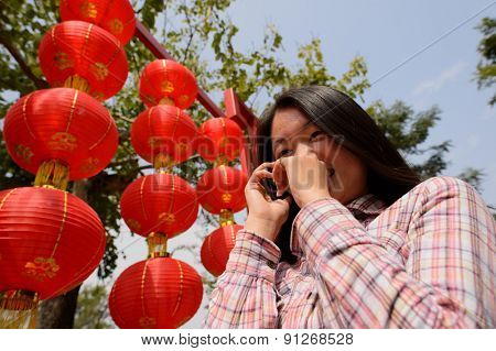 Chinese woman talking on cell phone during chinese new year