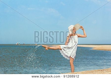 Girl Splashing Water On The Beach