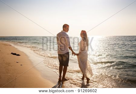 Bride And Groom At Edge Of Water Against Sun Rays