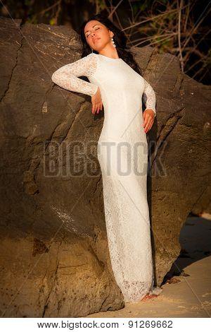 Bride Leans Against Rock On Beach