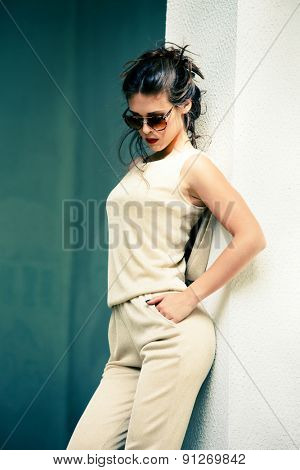 elegant summer fashion young woman wearing  golden overalls, hair in bun and sunglasses, shot in the city