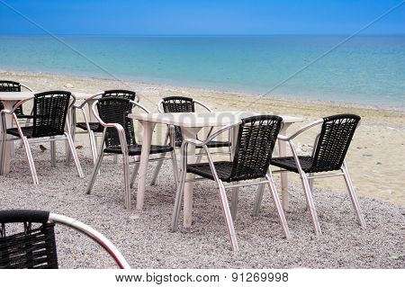 Beach cafe with empty tables and chairs placed at the sea waterfront