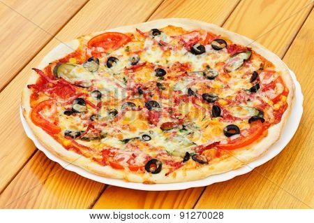 Whole pizza with cut pepperoni, black olives, corn, cheese and pickled cucumbers