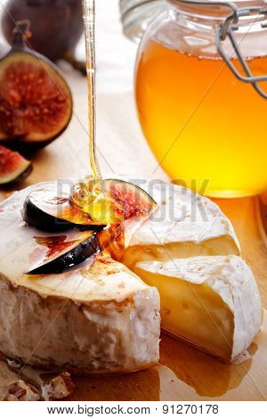 Brie Cheese and sliced Figs poured with honey on wood cheese-board