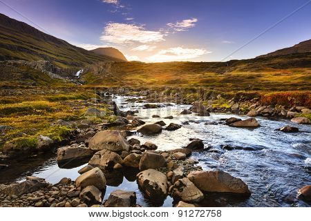 Scenic stream and waterfall in the valley by Seydisfjordur fjord at sunset