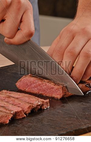 Cook slicing grilled beef steak on stone board.
