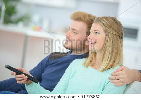 Happy young couple watching television