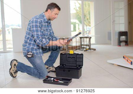 Builder kneeling by his toolbox