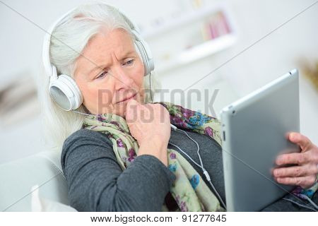 Senior lady listening to music through headphones