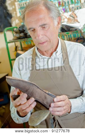 Cobbler holding shoe