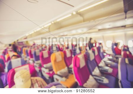 Blurred Image Interior Of Airplane With Passengers On Seats