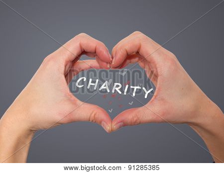 close up of woman hands in heart shape. Charity sign inside.