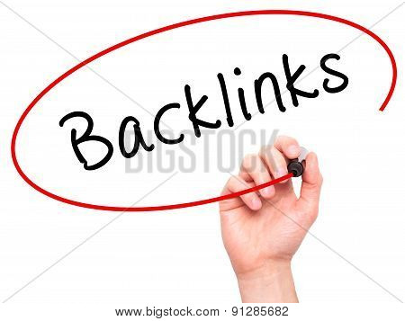Man Hand writing Backlinks with marker on transparent wipe board.