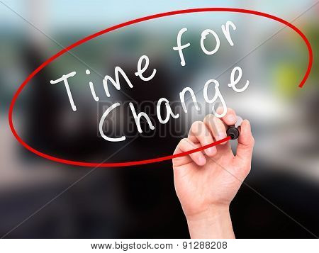Man Hand writing Time for Change with marker on transparent wipe board.