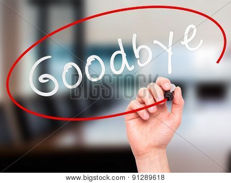 Man Hand writing Goodbye with marker on transparent wipe board.
