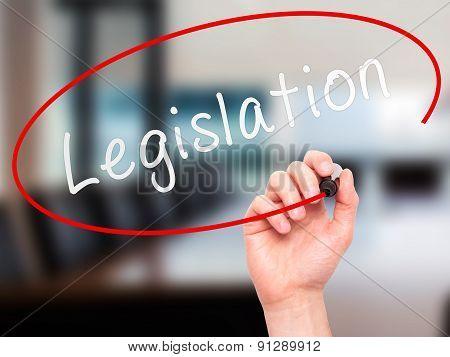Man Hand writing Legislation with marker on transparent wipe board.