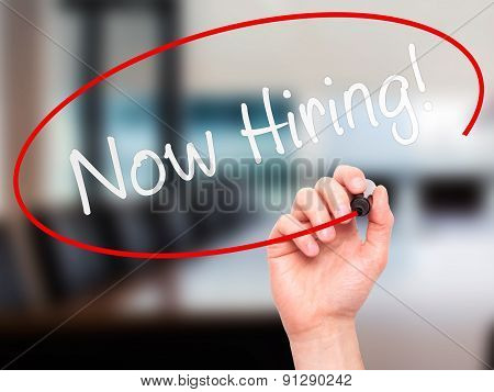 Man Hand writing Now Hiring! with marker on transparent wipe board.
