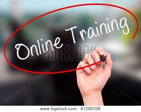 Man Hand writing Online Training with marker on transparent wipe board.