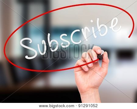 Man Hand writing Subscribe with marker on transparent wipe board.