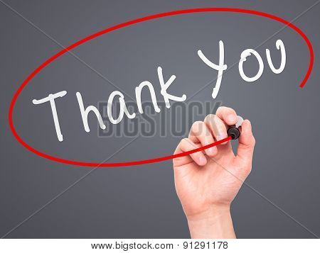 Man Hand writing Thank You with marker on transparent wipe board.