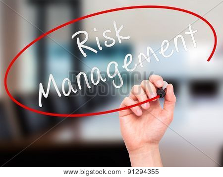 Man Hand writing Risk Management with marker on transparent wipe board.