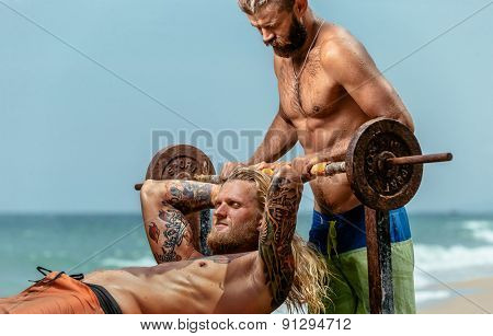 Two men doing weight lifting on sea beach