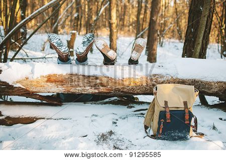 Couple Laying On The Ground In Winter Forest With Legs On The Tree