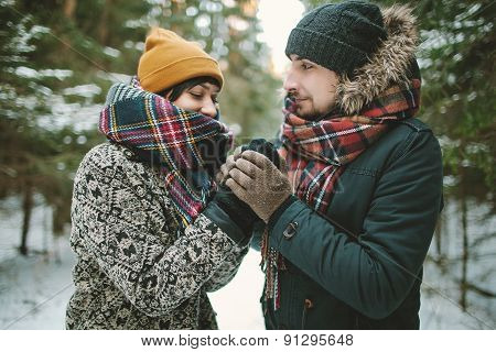 Young Man Holds His Girlfriends Hands In Winter Forest