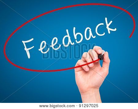 Man Hand writing Feedback with marker on transparent wipe board