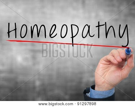 Man Hand writing Homeopathy with marker on transparent wipe board