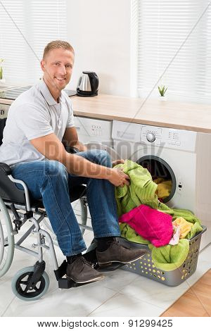 Man On Wheelchair Putting Clothes Into The Washing Machine