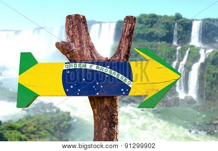 Brazil Flag wooden sign with Iguazu Falls on background