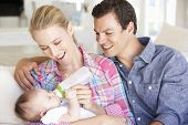 pic of feeding  - Young Family With Baby Feeding On Sofa At Home - JPG
