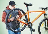 stock photo of bicycle gear  - Mechanic serviceman repairman installing assembling or adjusting bicycle gear on wheel in workshop - JPG
