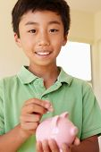 image of pre-teen boy  - Young boy putting money in piggybank - JPG