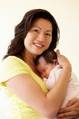 stock photo of cuddle  - Vietnamese mother cuddling baby - JPG