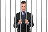stock photo of jail  - A handcuffed businessman in jail holding bars isolated on white - JPG