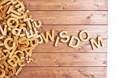 foto of piles  - Word wisdom made with block wooden letters next to a pile of other letters over the wooden board surface composition - JPG