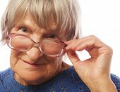 stock photo of old lady  - old senior lady looking through her eyeglasses isolated on white background - JPG