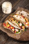 foto of sandwich wrap  - Tortilla wrap sandwiches with fried chicken and vegetables on wooden backgroundselective focus  - JPG