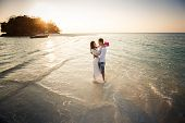 stock photo of barefoot  - bride and groom hug barefoot in shallow water at spit against sunrise - JPG