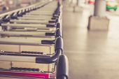 stock photo of trolley  - Close up trolleys luggage in a row in airport retro filter effect - JPG