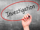 stock photo of investigation  - Man Hand writing Investigation with marker on transparent wipe board - JPG