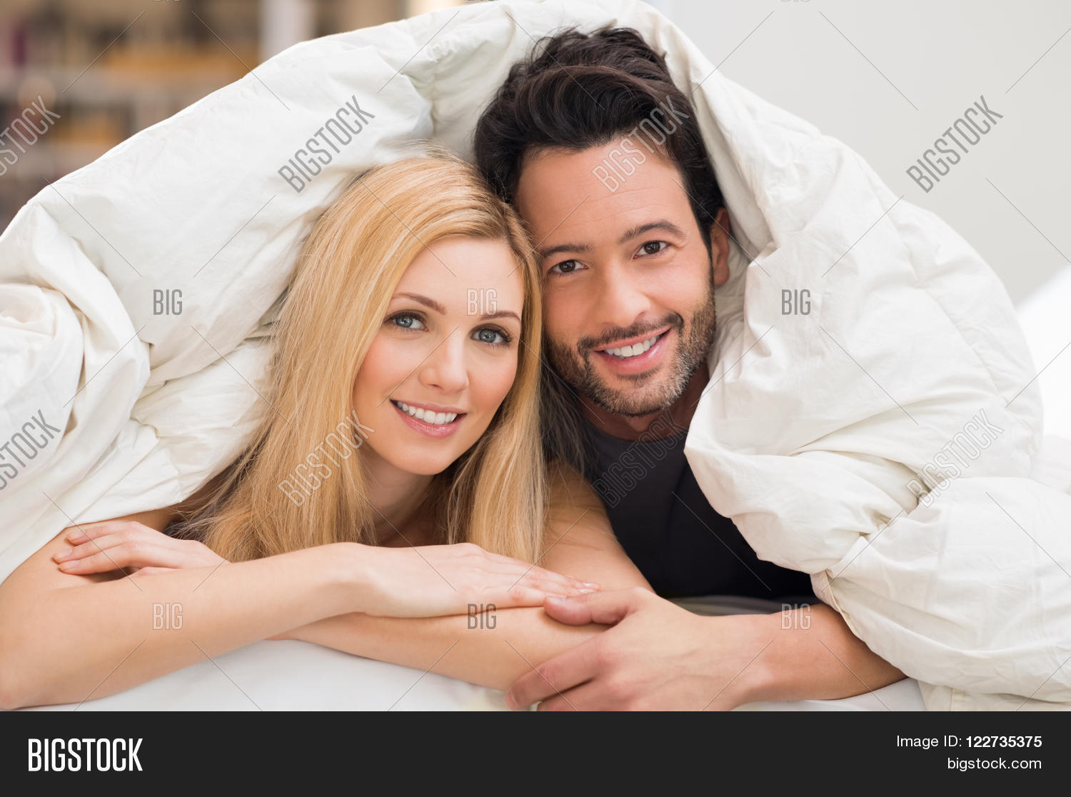 Cute romantic couple under a bed covers in the bed  Happy young couple  lying down. Cute romantic couple under a bed covers in the bed  Happy young