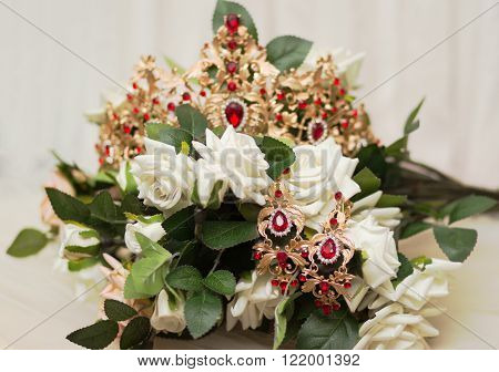 Bride golden crown with shining brilliants on rose bouquet